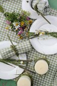Candles and posy of wildflowers arranged on green and white gingham tablecloth