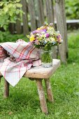 Vase of colourful wildflowers on vintage wooden stool in garden