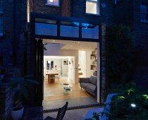 Blick von nächtlicher Terrasse in erleuchteten, offenen Wohnraum