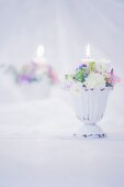 Romantic flower arrangement and lit candle in front of mirror
