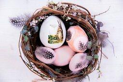 Osternest mit nostalgisch verzierten Eiern und Federn