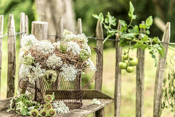 Wreath of hay and Queen Anne's lace in front of paling fence