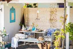 Set table and summery decorations on terrace with stone wall