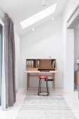 Simple desk and stool in niche below sloping ceiling