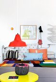 Gelber Tisch mit Lavaschale vor einem Sofa mit bunten Kissen
