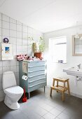 Old chest of drawers in simple bathroom