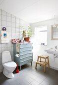 Schlichtes Badezimmer mit einer alten Kommode