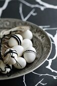 Hens' eggs decorated in black and white in antique silver dish