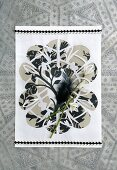 Paper artwork decorated with snowdrops and black feathers