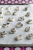 Unbaked poppyseed and puff pastry swirls on baking sheet