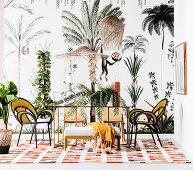 Esstisch mit leichten Stühlen vor Tapete mit Dschungelmotiv