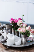 Tin cup with roses and candles on tray