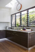 Modern kitchen with dark wooden fronts and louvre windows
