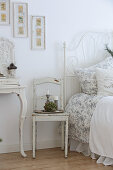 Ornate metal bed in white, vintage-style bedroom