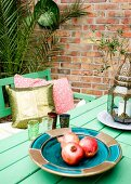 Oriental accessories on garden table against brick wall