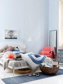 Schlafzimmer in Blautönen mit lachsfarbenem Polstersessel, Standspiegel und Körben beim Bett