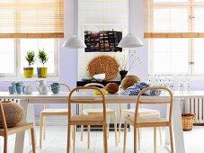 Nordischer Essbereich mit langem weissem Esstisch und naturbelassenen, modernen Holzstühlen