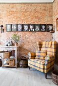 Tartan wing-back chair in front of family photos on brick wall