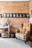 Karierter Ohrensessel vor einer Backsteinwand mit Familienbildern