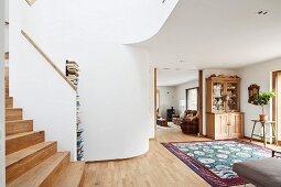 Offener Wohnraum mit Holztreppenaufgang und Durchgang, Blick auf Geschirrschrank