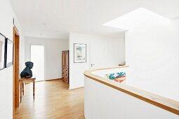 Helles Obergeschoss mit weisser Brüstung, Eichenparkett und Oberlicht
