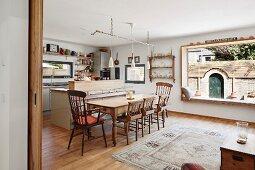 Offene Küche mit traditionellen Holzmöbeln am Essplatz und modernem Panoramafenster