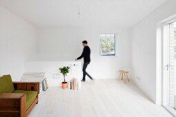Helles Dachgeschosszimmer mit weißem Dielenboden und grünem Vintage-Lesesessel; Mann im Hintergrund am Treppenabgang