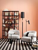 Two pale armchairs on black and white rug in front of bookcase and pink wall