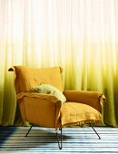 Yellow armchair in front of yellow ombré curtain