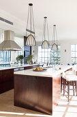 Drei Hängeleuchten über der Kücheninsel aus dunklem Holz