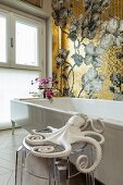 Octopus ornament on transparent stool next to bathtub