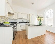 A natural white country house kitchen with a breakfast bar in an old building with round arch windows