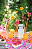 Colourful arrangement of flowers and orange candles