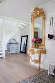 Opulent gilt-framed mirror on Baroque console in foyer