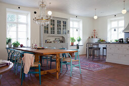 Dining table and blue designer chairs in country-house kitchen-dining room