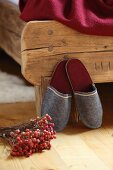 Grey felt slippers leant against rustic wooden bed