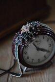 Glass-bead jewellery on vintage alarm clock