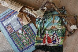 Ancient craft of beading: bag with courtly scene next to instruction book