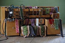 Hand-made glass-bead jewellery draped over jewellery box