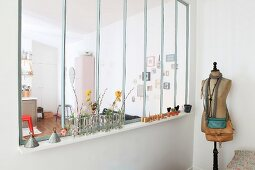 Handbags on vintage tailors' dummy and small vases of flowers on interior windowsill