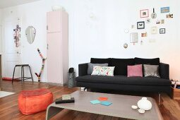 Black couch, coal scuttle, pink retro cabinet and orange pouffe in open-plan living area