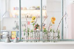 Flower arrangement against interior window with view into kitchen