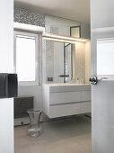 Blick ins helle Bad mit silbernem Mosaik und weißen Möbeln
