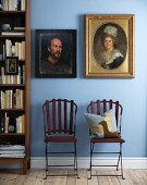 Two antique-style portraits in different frames on light blue wall