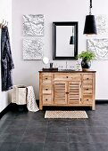 Vanity unit made of wood with black granite top, wall mirror and maps on canvas in a masculine bathroom with