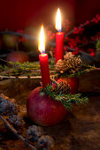 Christmas arrangement of candles in apples and larch branches