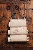 Hand-sewn magazine rack hanging from vintage coat hanger on wooden door
