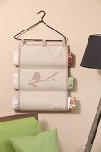 Hand-sewn magazine rack hanging from vintage coat hanger on wall