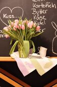 Vase of tulips, tea towels with Easter motifs and coffee service on wooden table against chalkboard with chalk messages
