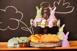 Pastries and pink and lilac Easter ornaments on cake stand against chalkboard wall
